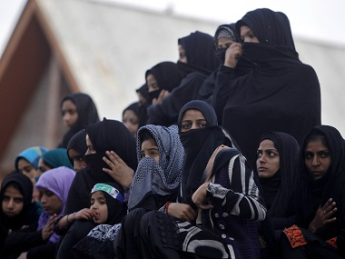 Kashmiri Shi'ite Muslim women and girls watch a Muharram procession ahead of Ashura in Srinagar