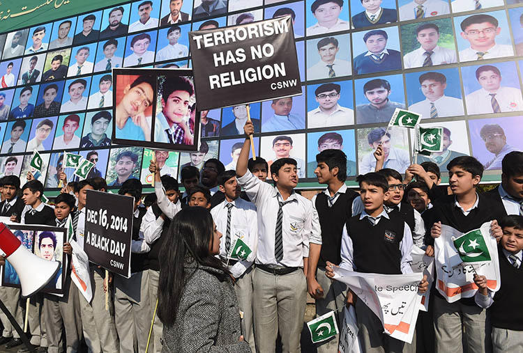 Students and activists gather by images of the victims of the 2014 Peshawar school massacre. A military crackdown after the attack helped reduce violence against  the press, but increased self-censorship, journalists say