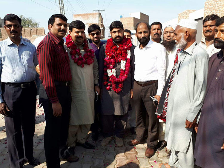 Authorities detained Hafiz Husnain Raza, pictured center in garland